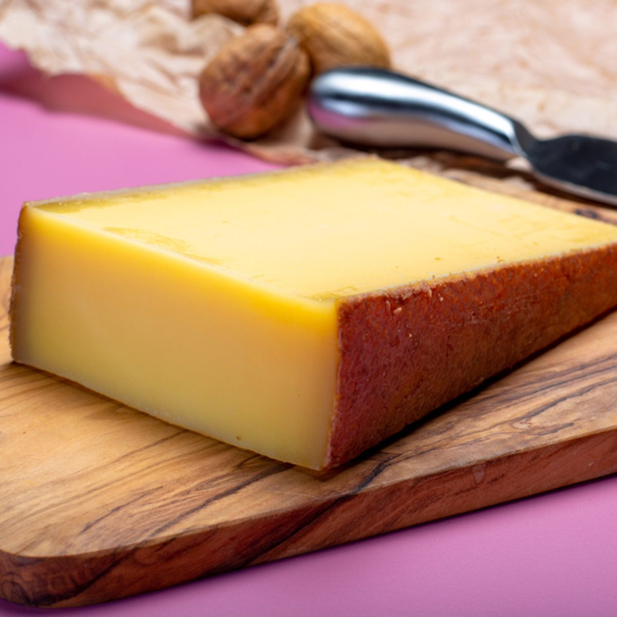 Piece of aged Comte or Gruyere de Comte, AOC French cheese made from unpasteurized cow's milk in the Franche-Comte region of eastern France with traditional methods of production close up.