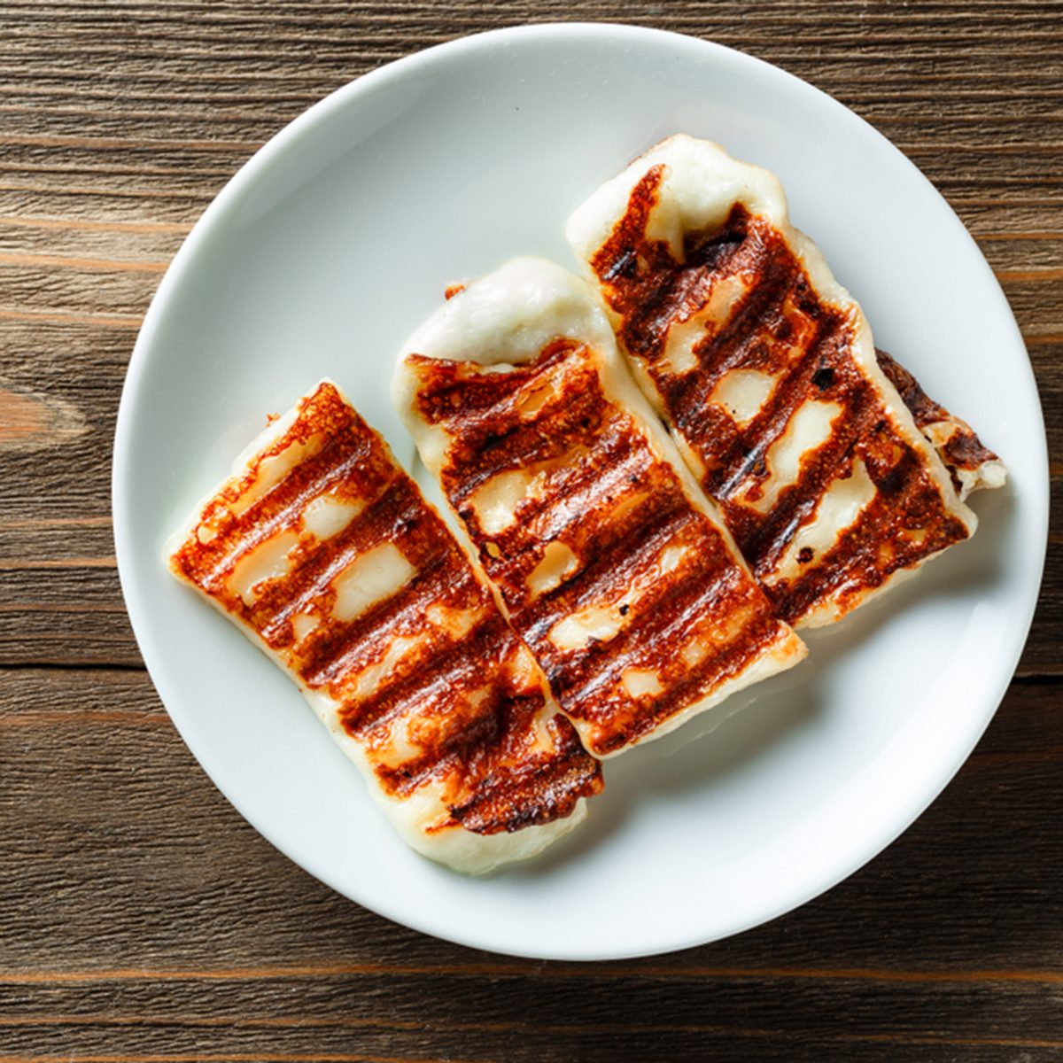 Traditional Greek Grilled Hallumi Cheese on white plate on wooden background.