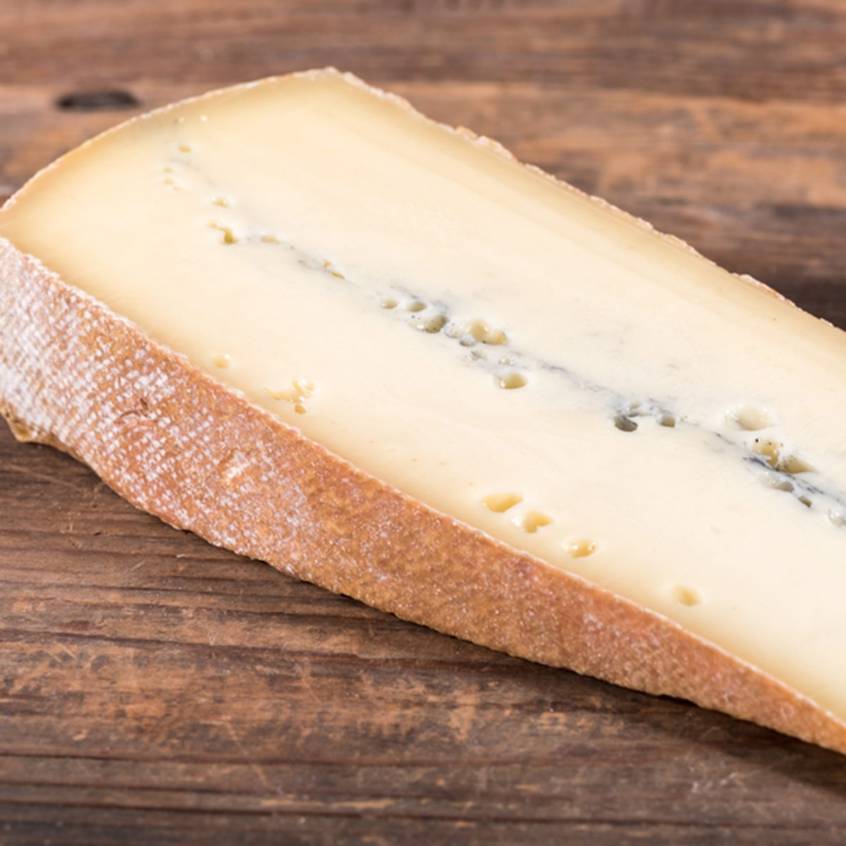French morbier cheese, on wooden background