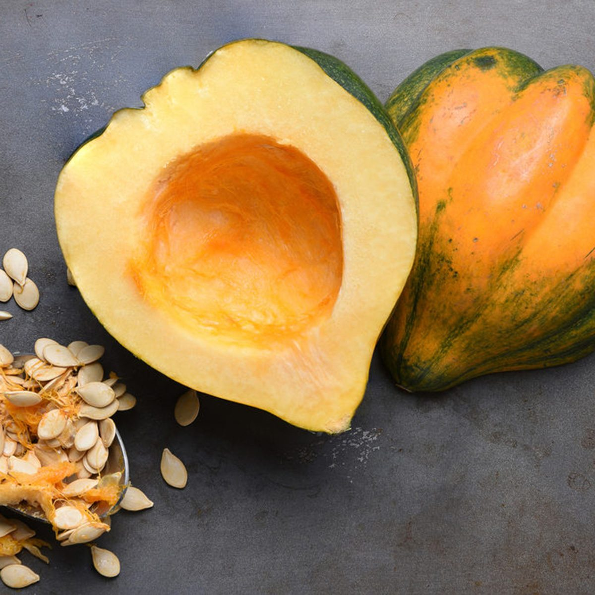 High angle view of an Acorn Squash cut in half on a metal baking sheet with a spoon and seeds scooped out.