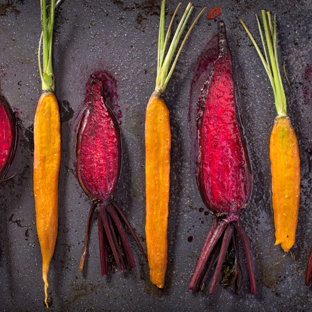 Roasted beets and carrot on baking tray top view