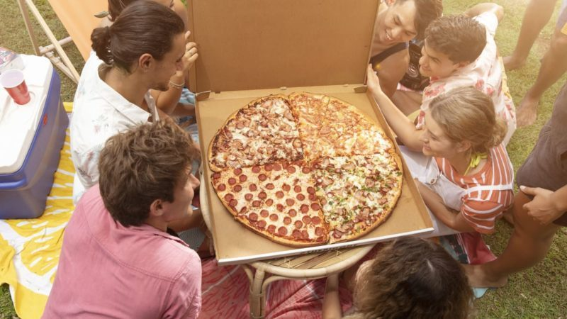Huge Dominos pizza being held up by a group of people