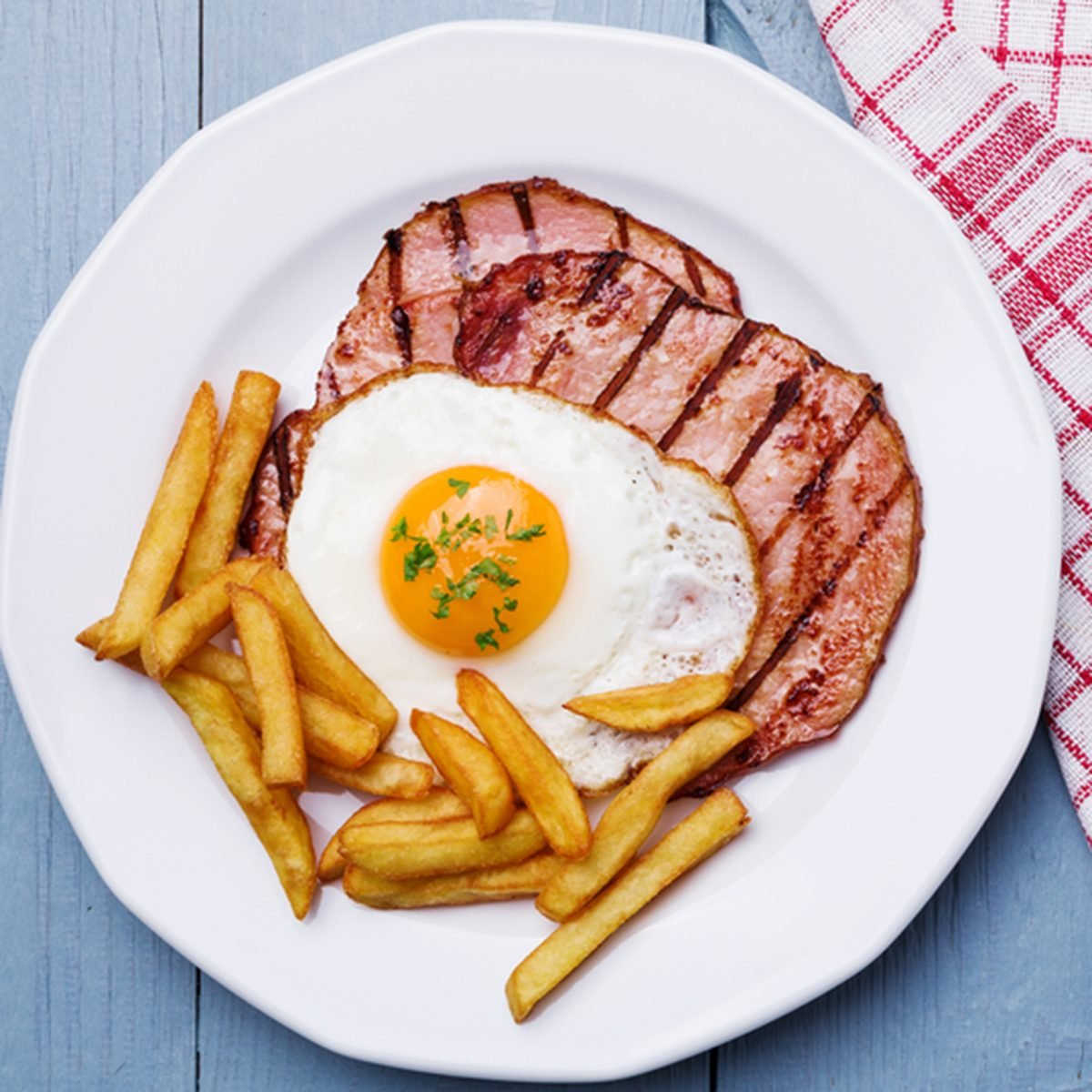 English breakfast with grilled ham, fried egg and french fries.