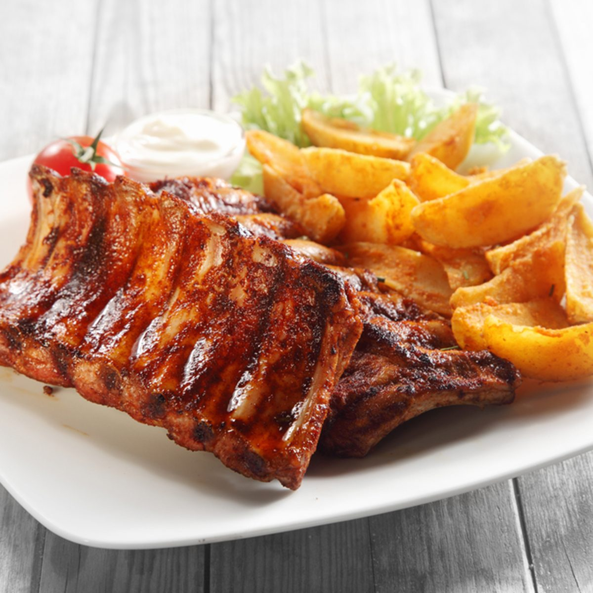 Close up Gourmet Main Dish with Grilled Pork Rib and Fried Potatoes on White Plate.