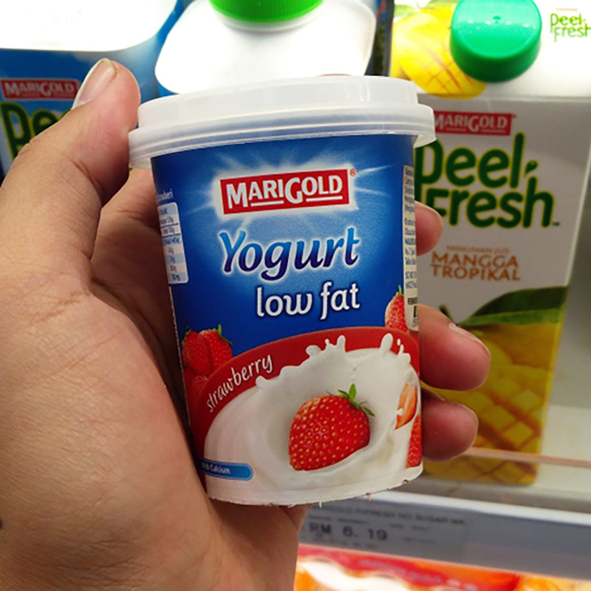 KLANG, MALAYSIA - APRIL 1, 2018 : Hand holding a cup of Marigold Low Fat Yogurtin hypermarket.