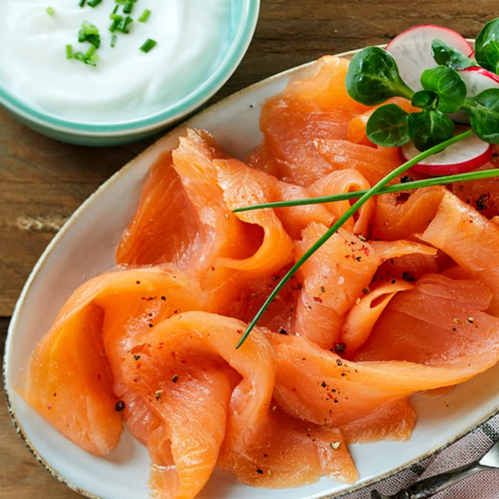 Fresh slices of healthy smoked salmon or lok served with a creamy chive sauce on an oval platter viewed from above on wood with copy space