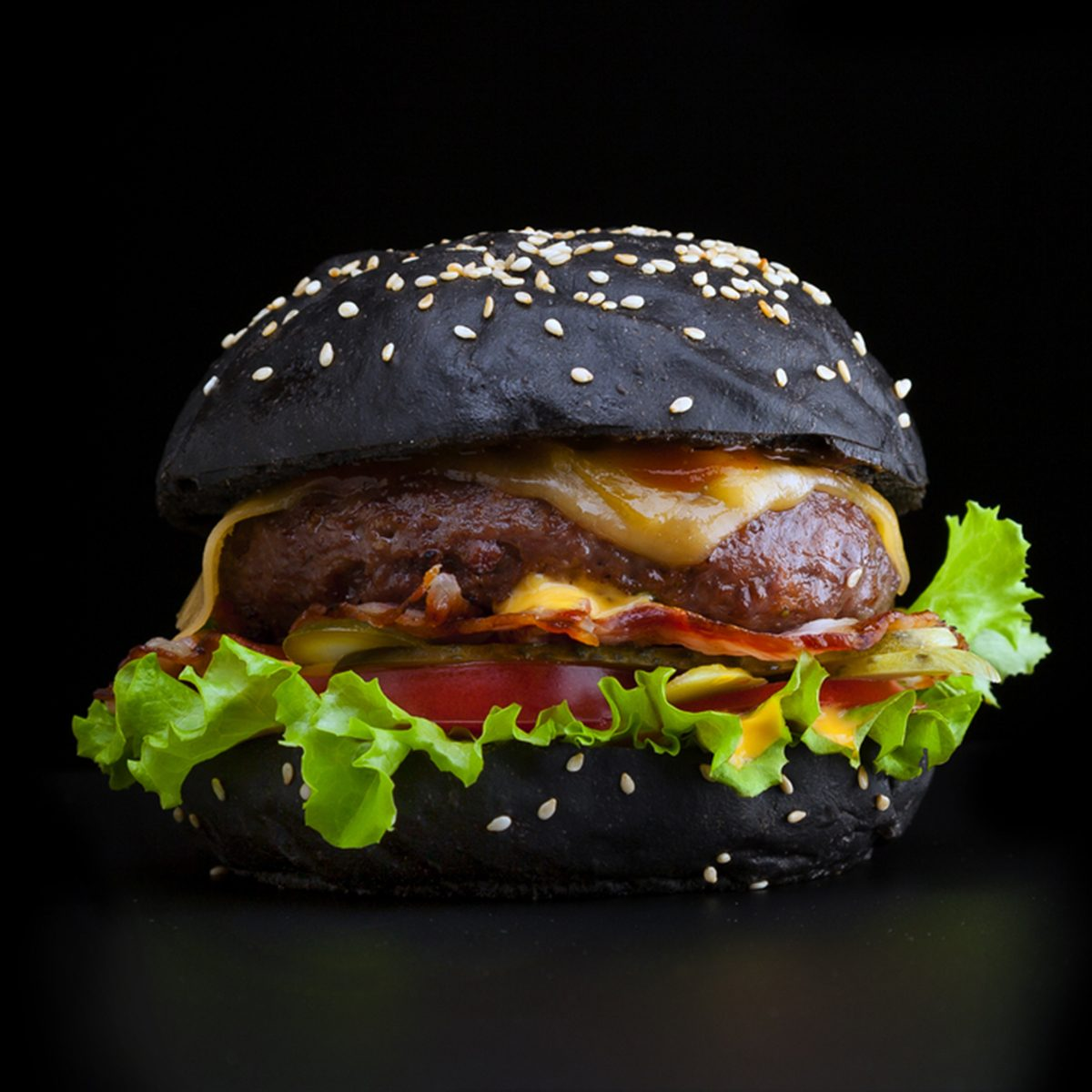 Tasty and appetizing hamburger isolated black with a black bun and bacon.