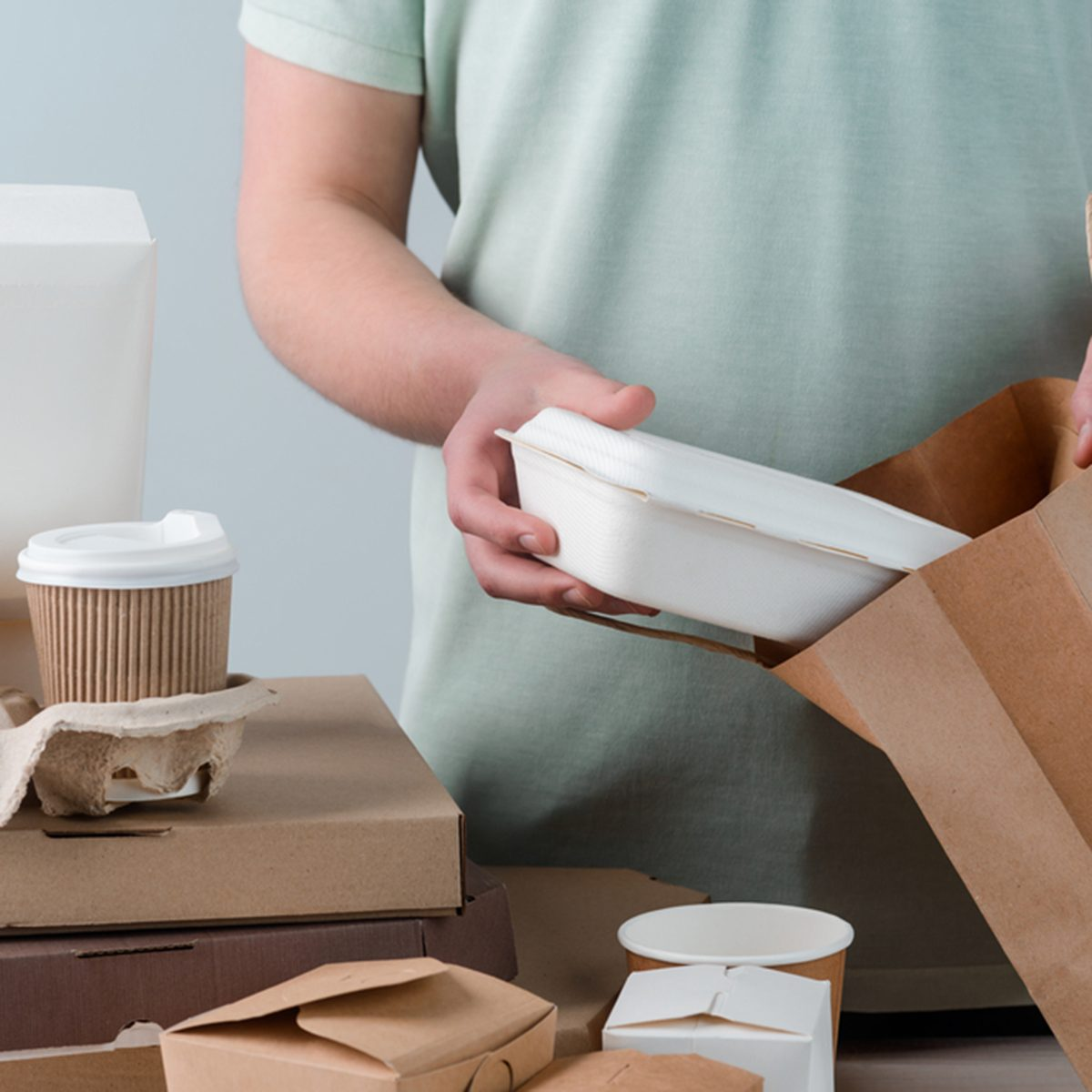 Male hands putting take-out food container into paper bag, close-up.