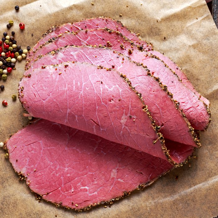Peppered roast beef pastrami slices on paper with grains of coloured pepper.