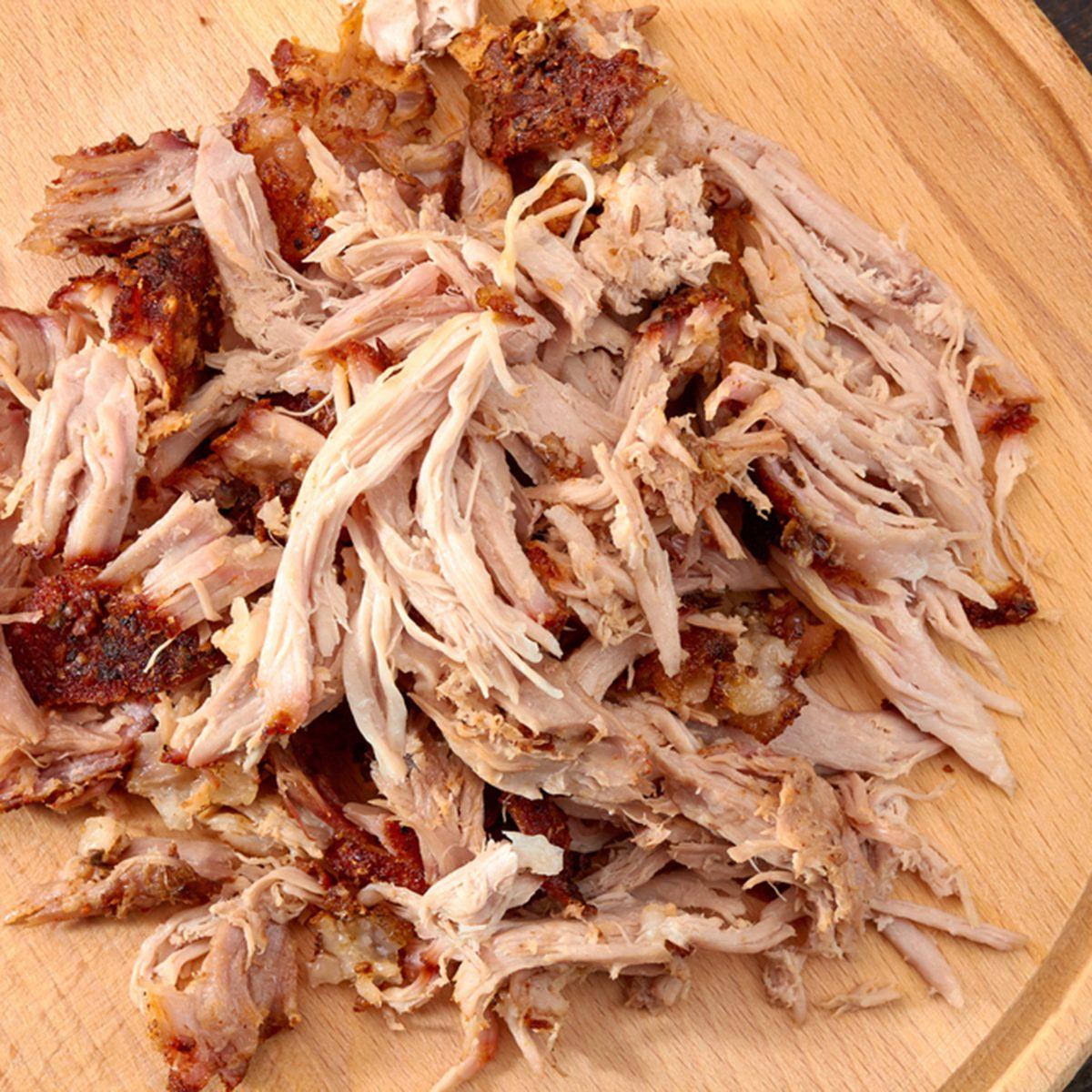 Pulled pork on round wooden board