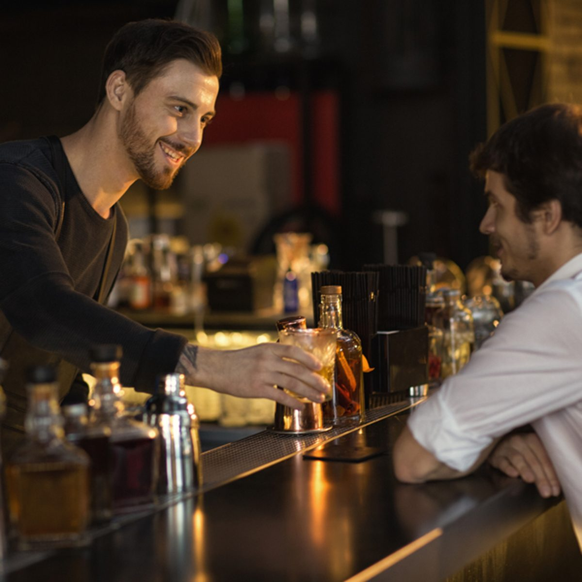 Cheerful male bearded bartender smiling giving his client a drink while working at the bar communication friendly positivity entertainment leisure occupation job luxury lifestyle club weekend service; Shutterstock ID 1010959540; Job (TFH, TOH, RD, BNB, CWM, CM): TOH