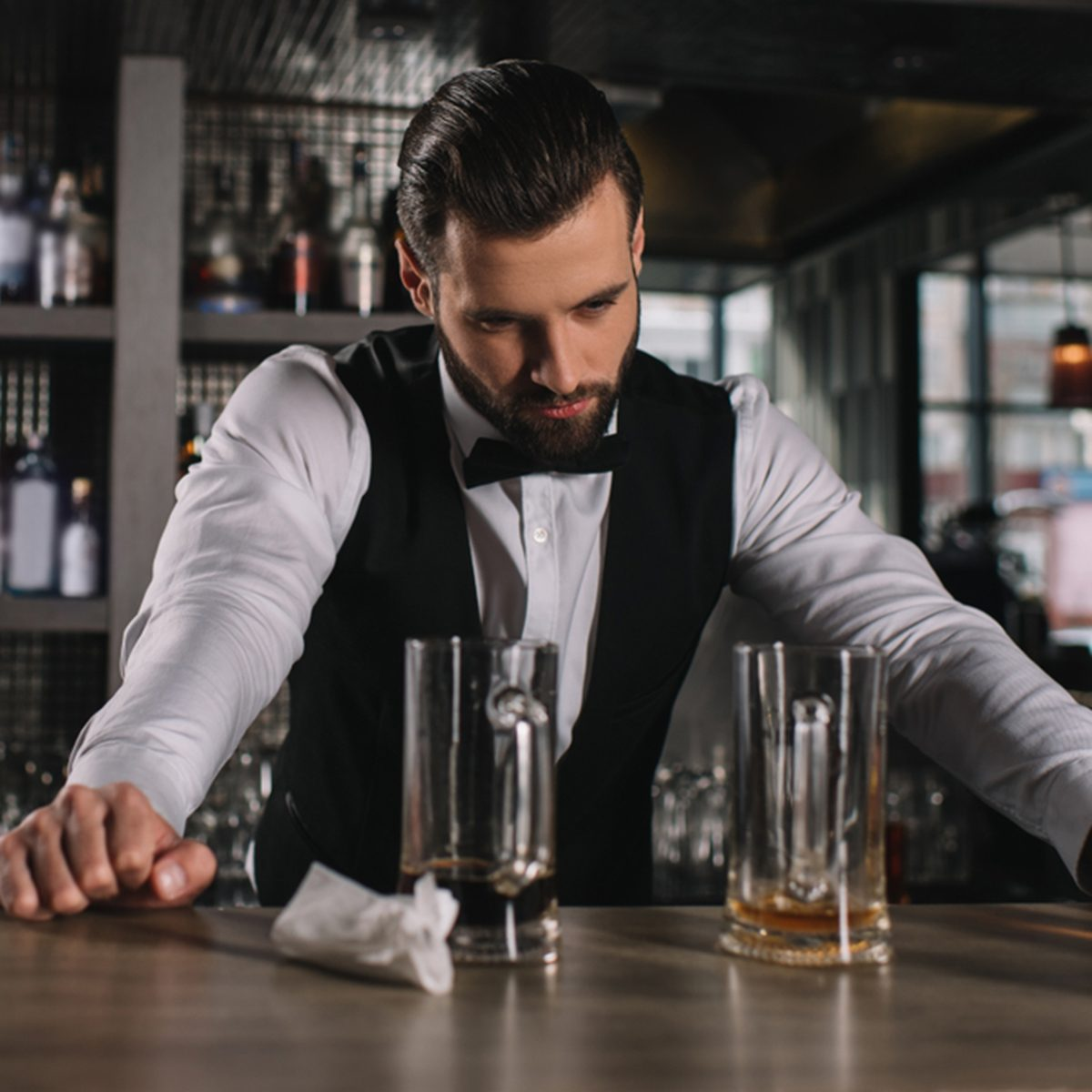 tired handsome bartender leaning on bar counter and looking at dirty glasses and trash; Shutterstock ID 1034501887; Job (TFH, TOH, RD, BNB, CWM, CM): TOH