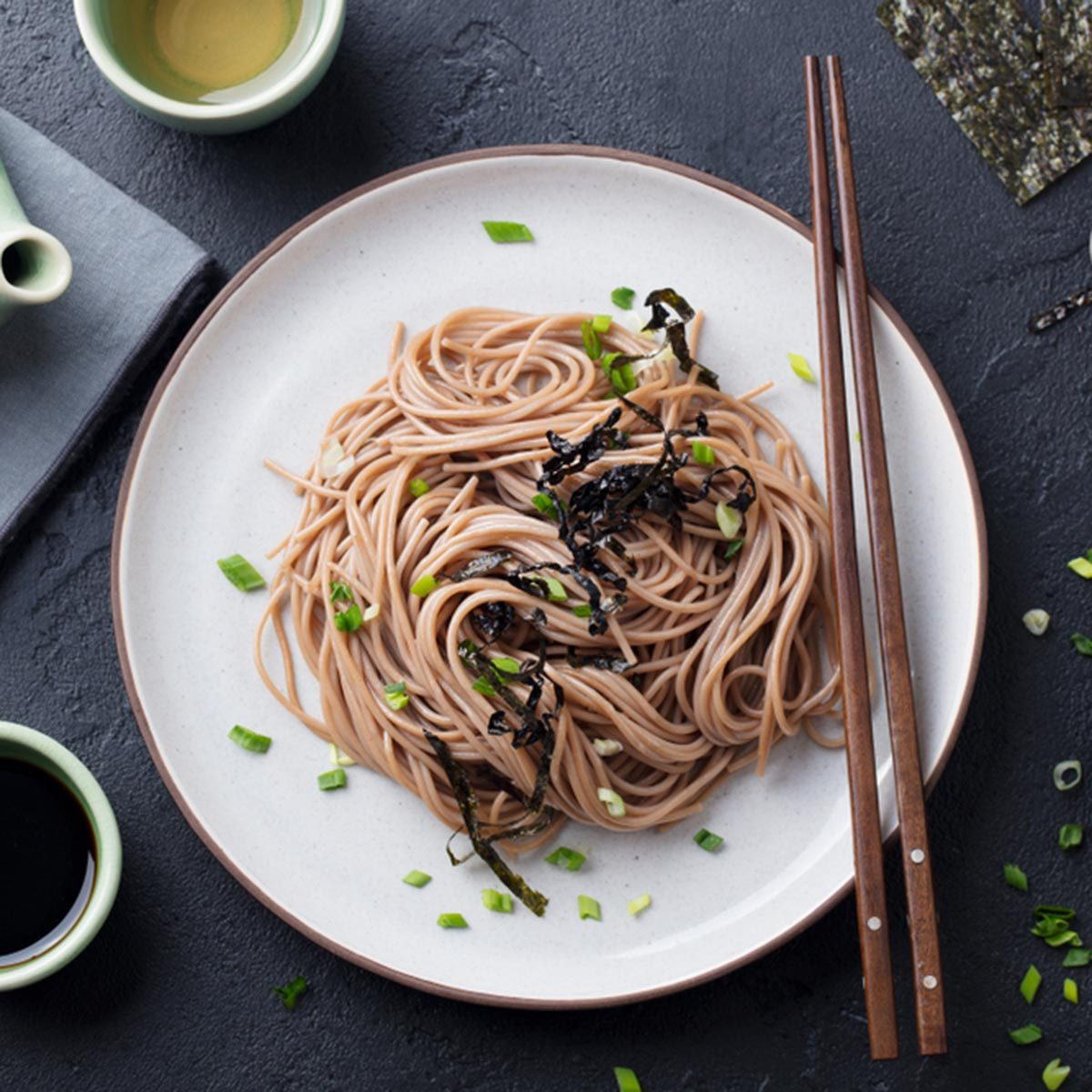 Soba noodles with sauce and garnishes. Japanese food. Top view. Black slate background.; Shutterstock ID 1100194787; Job (TFH, TOH, RD, BNB, CWM, CM): TOH
