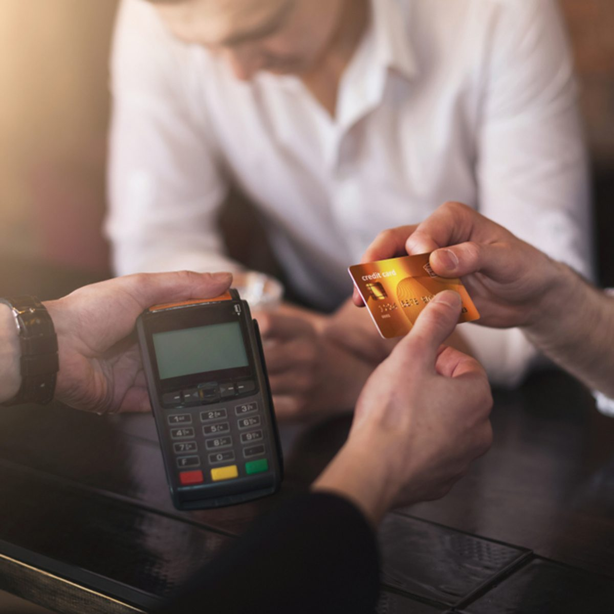 Drunk man paying via credit card, buying drinks in bar with bartender handing pos-terminal, copy space; Shutterstock ID 1129326635; Job (TFH, TOH, RD, BNB, CWM, CM): TOH