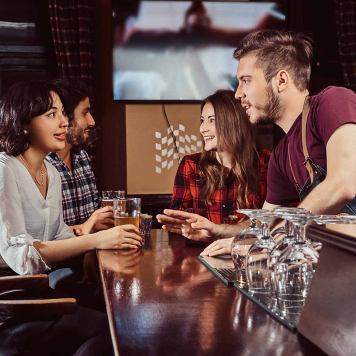 Group of happy multiracial friends resting at bar and talking with the bartender.; Shutterstock ID 1195313740; Job (TFH, TOH, RD, BNB, CWM, CM): TOH