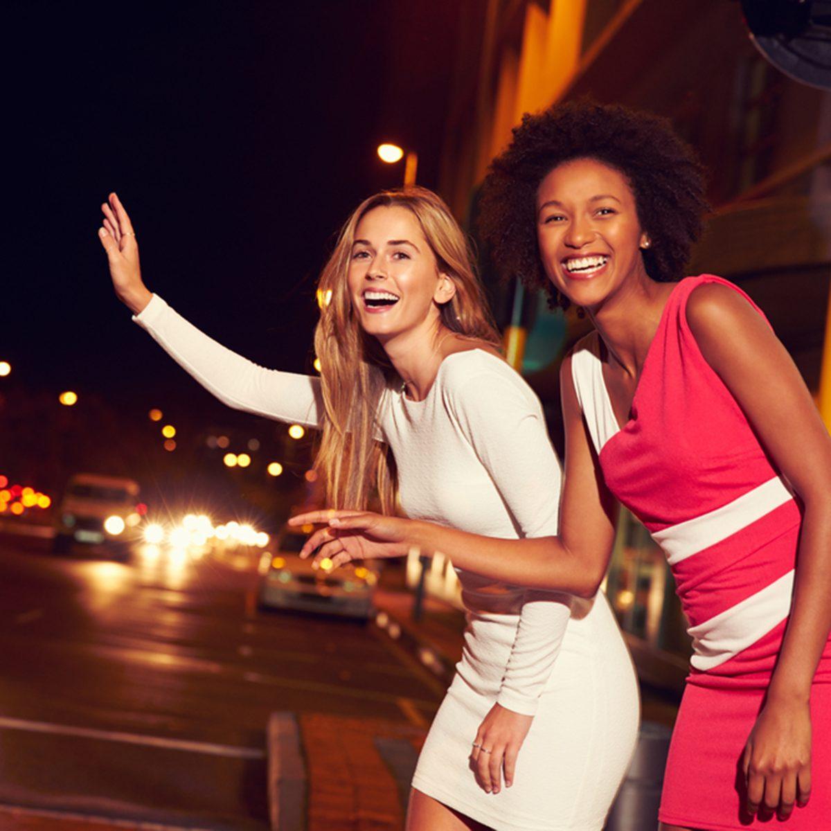 Female friends hailing taxi on city street at night; Shutterstock ID 289805144; Job (TFH, TOH, RD, BNB, CWM, CM): TOH