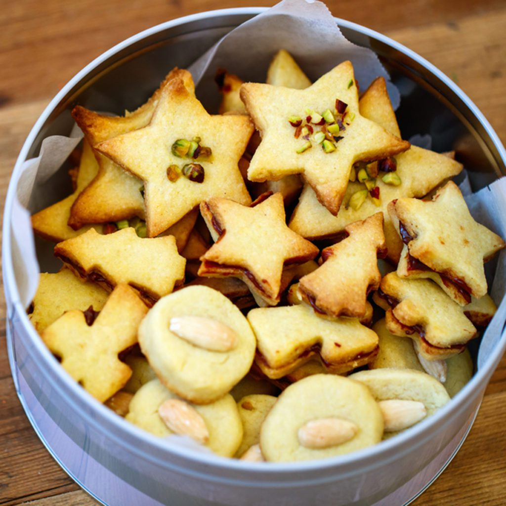 Freshly baked homemade Christmas cookies in a tin box, wooden background; Shutterstock ID 349993319