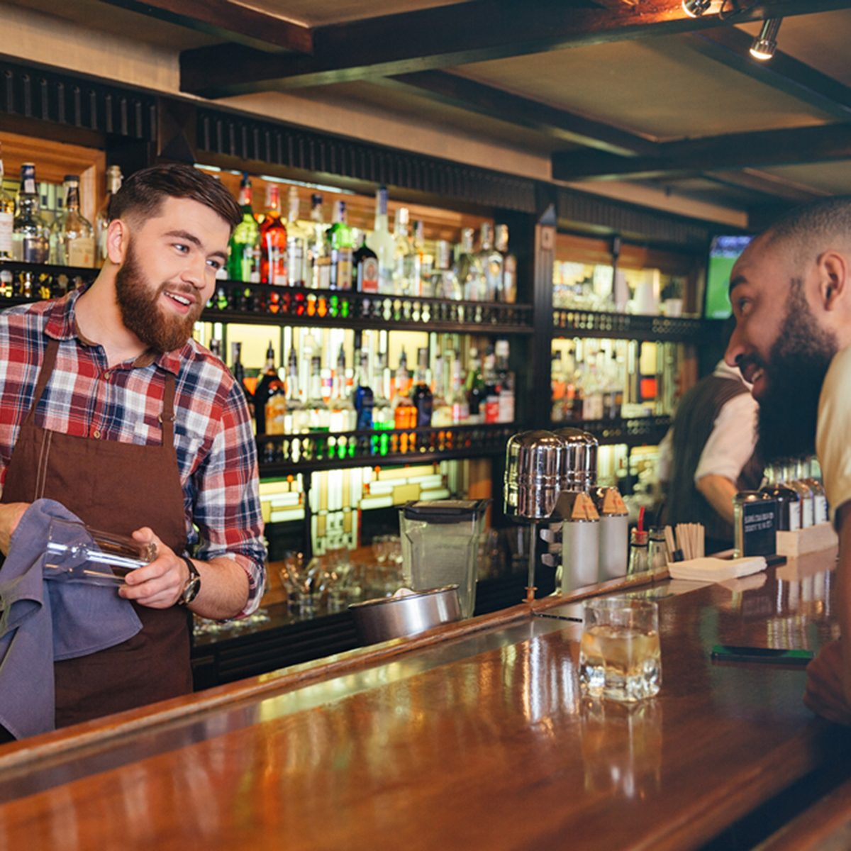 Smiling attractive young barman wiping glasses and talking to african american young man in bar; Shutterstock ID 521293036; Job (TFH, TOH, RD, BNB, CWM, CM): TOH