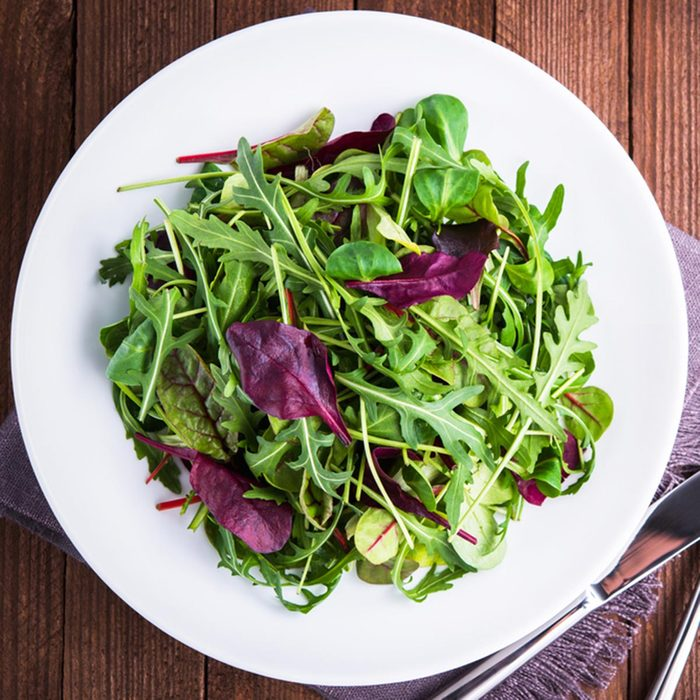 Fresh salad plate with mixed greens (arugula, mesclun, mache) on dark wooden background top view. Healthy food. Green meal.; Shutterstock ID 534979237; Job (TFH, TOH, RD, BNB, CWM, CM): TOH