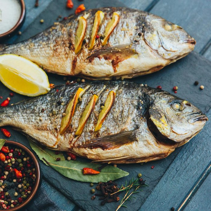 Delicious grilled sea bream fish with rosemary, lemon and peppercorns on wooden background. Culinary healthy cooking.; Shutterstock ID 577296571; Job (TFH, TOH, RD, BNB, CWM, CM): TOH