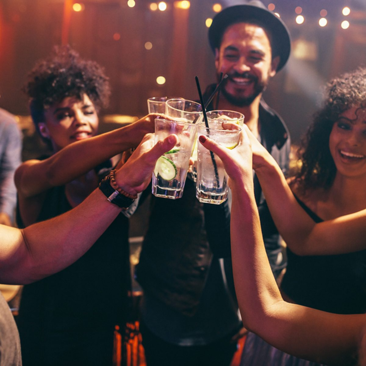 Group of friends having drinks at the night club party. Young people enjoying at a bar toasting cocktails.; Shutterstock ID 580144114