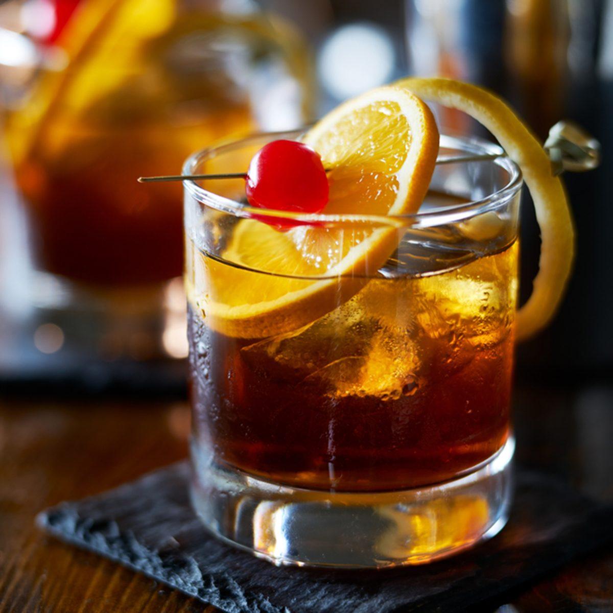 tasty alcoholic old fashioned cocktail with orange slice, cherry, and lemon peel garnish; Shutterstock ID 583137544; Job (TFH, TOH, RD, BNB, CWM, CM): TOH