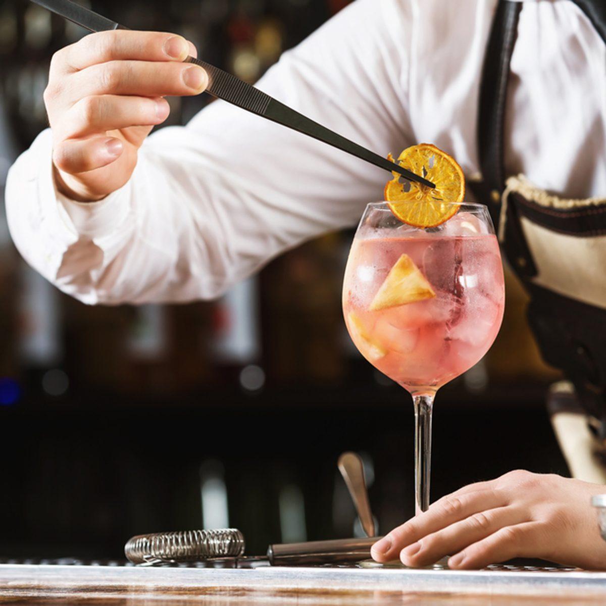 Elegant bartender is preparing pink cocktail holding orange chips at bar counter background.; Shutterstock ID 641031601; Job (TFH, TOH, RD, BNB, CWM, CM): TOH