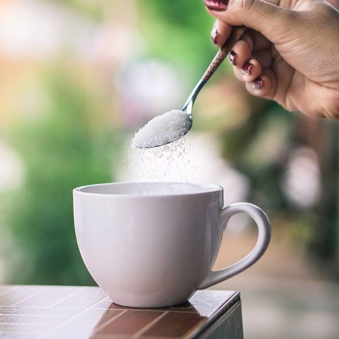sugar alternatives Unhealthy Woman Hand Holding Spoon Pouring Sugar 1205964143 Square
