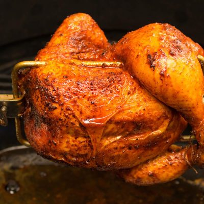 Charred rotisserie chicken over open flames in a barbecue.