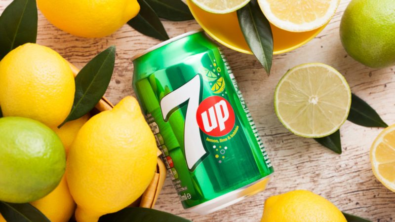 Aluminium can of 7UP lemonade soda drink with fresh lemons and limes.