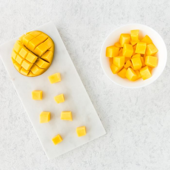 Top view of cut mango half and mango cubes on white marble cutting board and in white bowl.