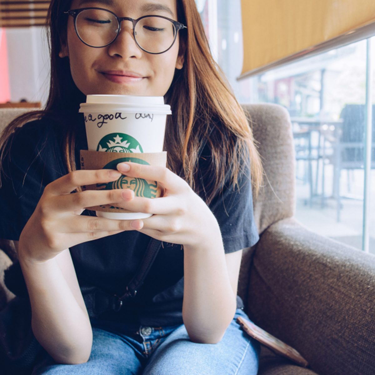 Chiang Rai, Thailand : May-23-2018 : Happy Asian girl holding a paper cup of Starbucks coffee in Starbucks coffee store.; Shutterstock ID 1101144779; Job (TFH, TOH, RD, BNB, CWM, CM): TOH