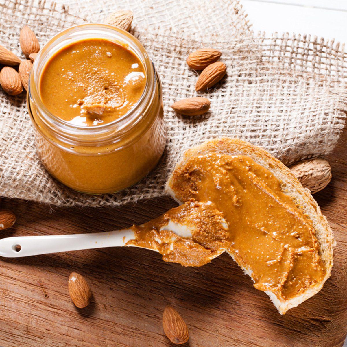 Homemade almond butter in jar on cutting board.
