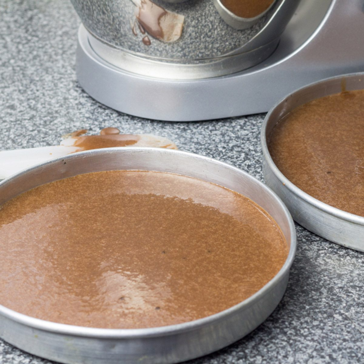 Cake pans with chocolate batter and mixer in background