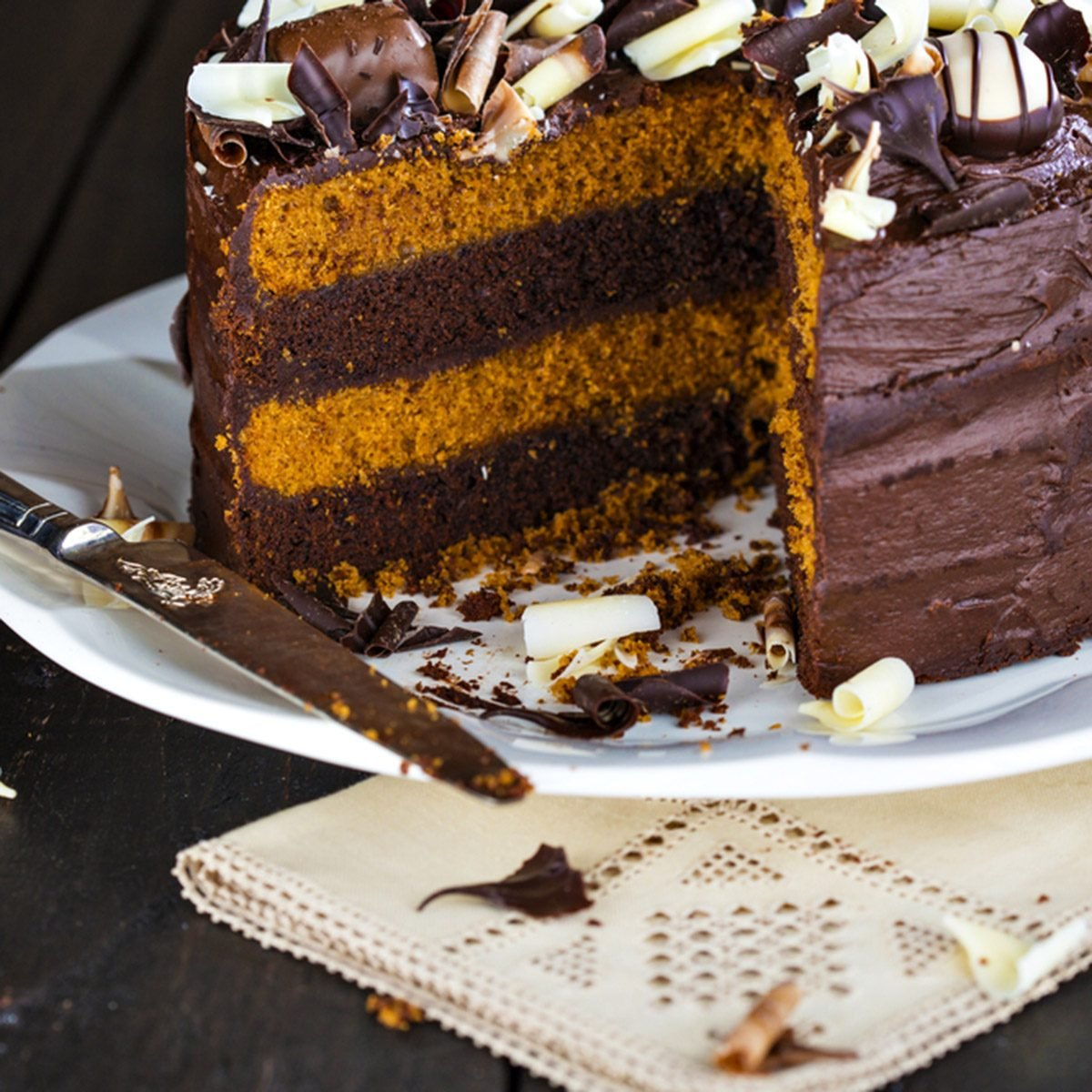 Luxury chocolate and toffee layer cake with a slice cut of it.