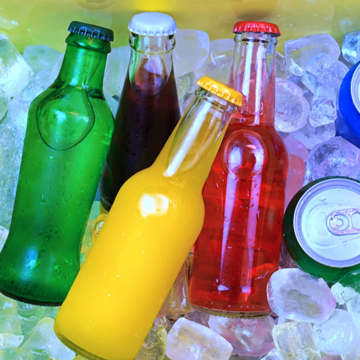 Colorful cold soda drinks, filled ice cubes in a coolbox
