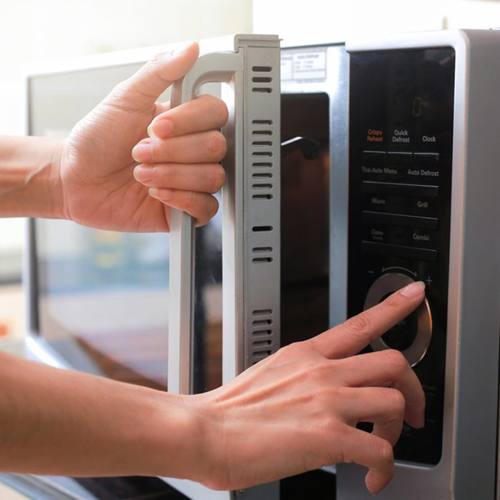 Woman's Hands Closing Microwave Oven Door And Preparing Food in microwave.