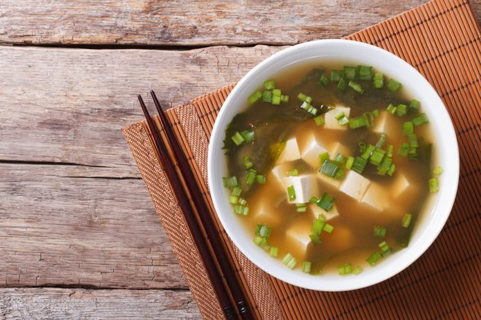 Japanese miso soup in a white bowl on the table.