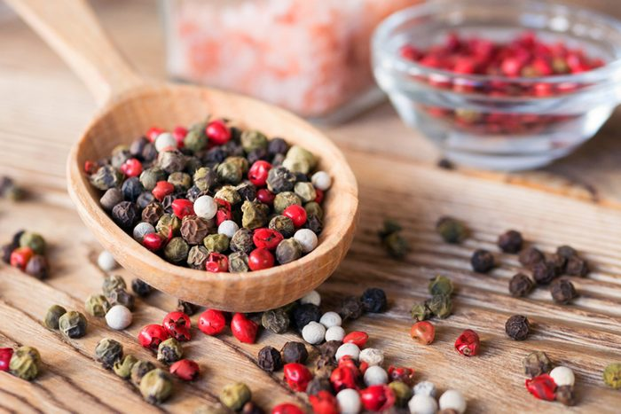 Mix of peppercorns in wooden spoon on rustic background with pink salt in glass jar.