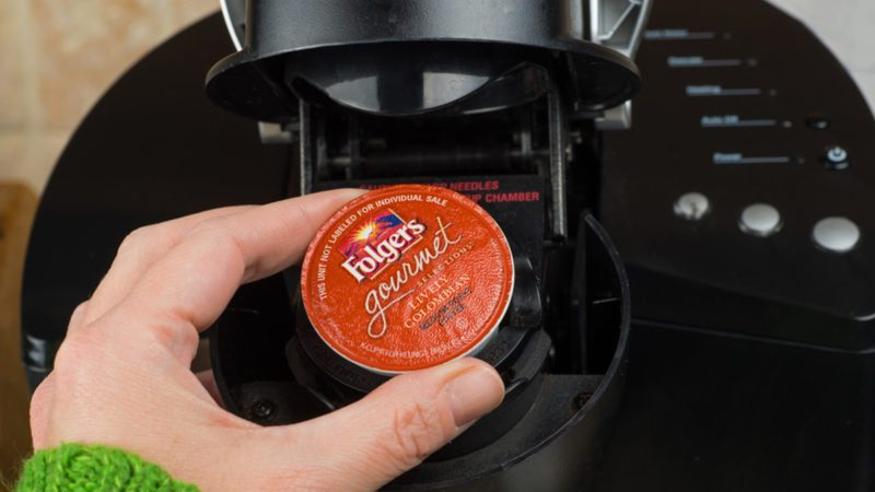 ATLANTA, GA -- FEB 14, 2014: Close-up of woman inserting single-serve K-cup Foldger's coffee into a Keurig coffee maker. ; Shutterstock ID 176711798; Job (TFH, TOH, RD, BNB, CWM, CM): Taste of Home