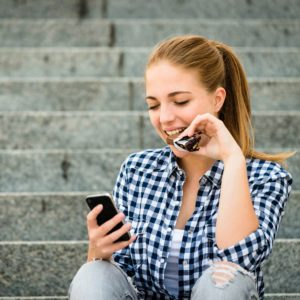 Teenager - young woman eating chocolate in street and looking in phone; Shutterstock ID 225964021; Job (TFH, TOH, RD, BNB, CWM, CM): TOH
