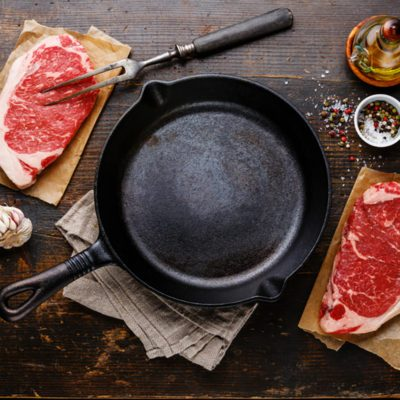 Raw fresh meat Steak Striploin for two with condiments around iron frying pan