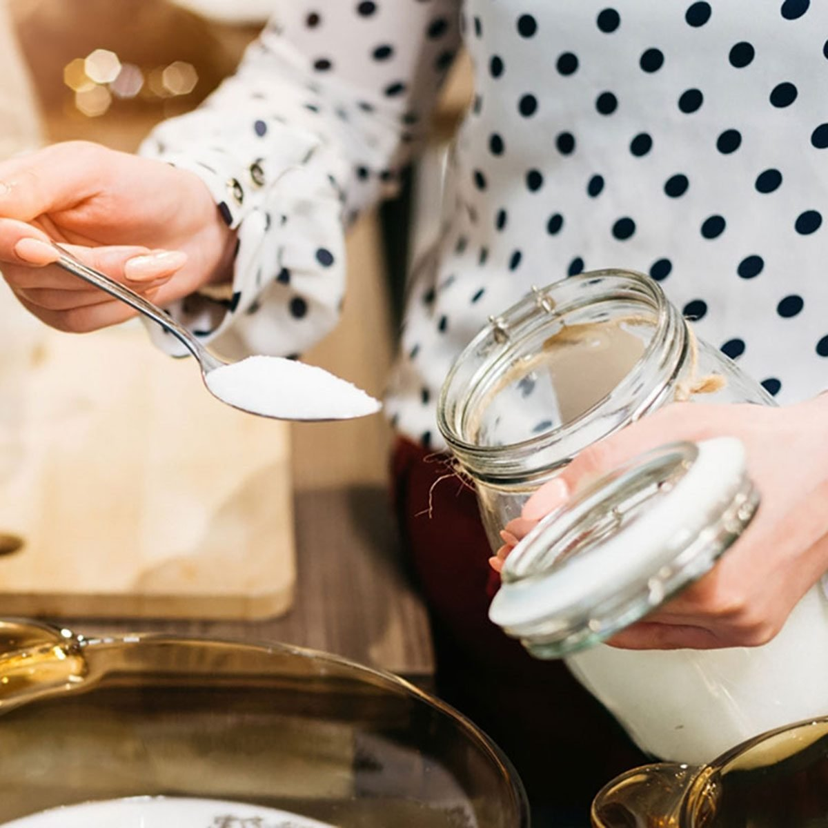 Woman cafe worker adding sugar to bowl with dessert ingredients.