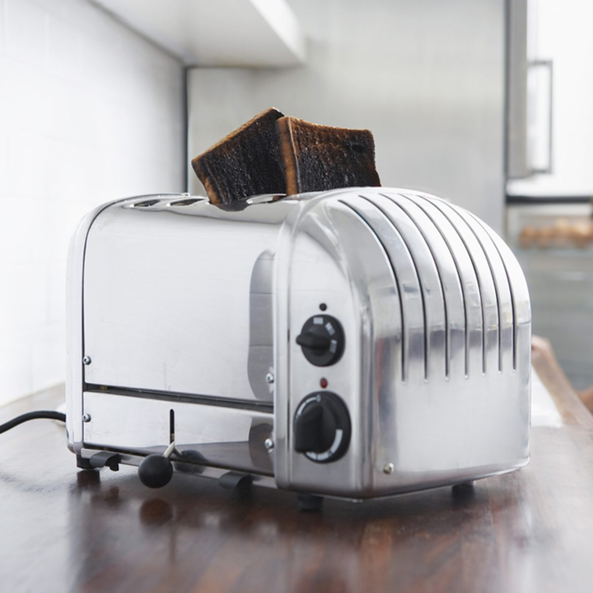 Burned toasts in toaster on kitchen counter with woman in background
