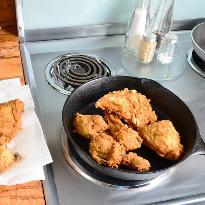 Chicken frying in old cast iron skillet on modern electric range with some on paper towels ready to serve.