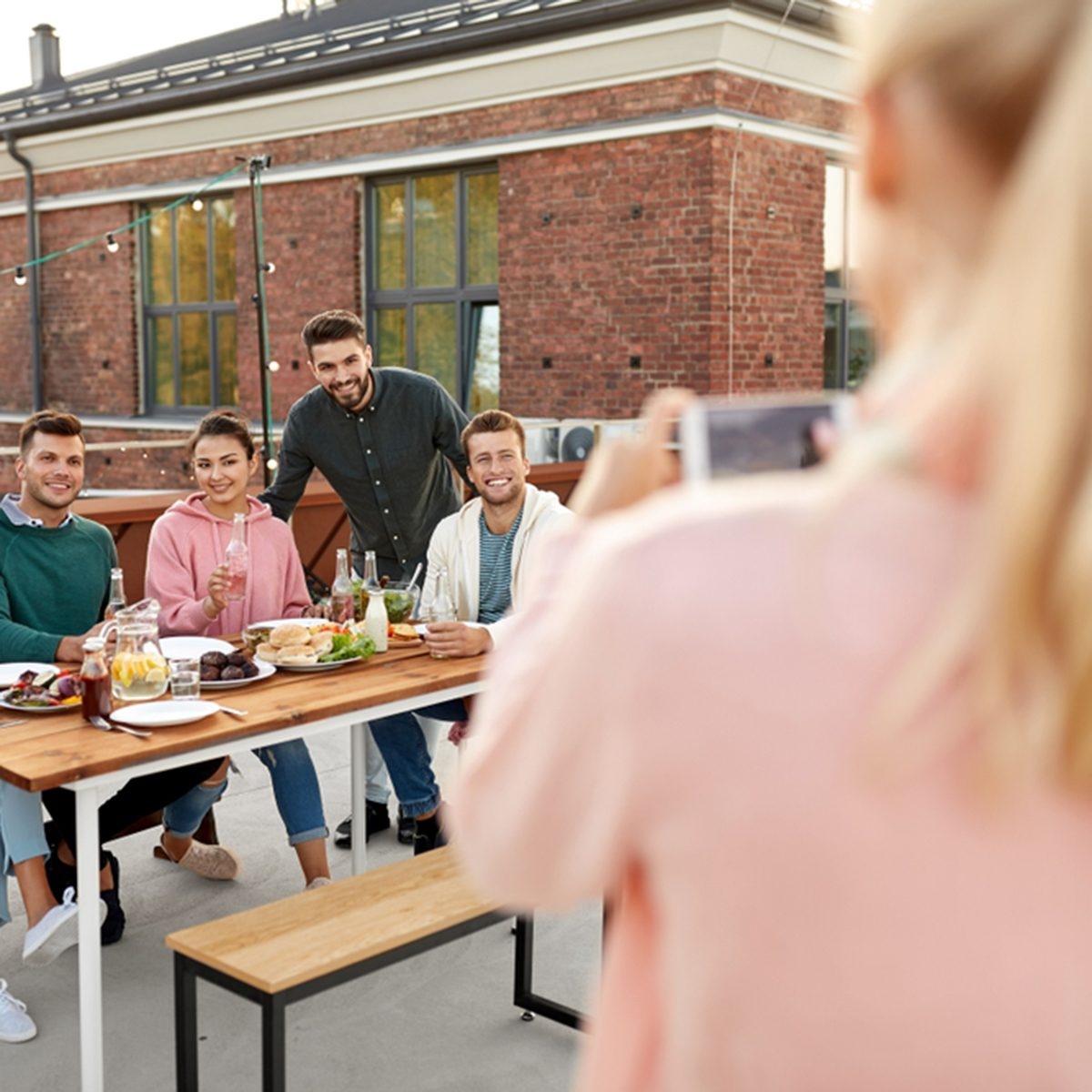 happy friends with non alcoholic drinks having barbecue party on rooftop in summer and photographing by smartphone