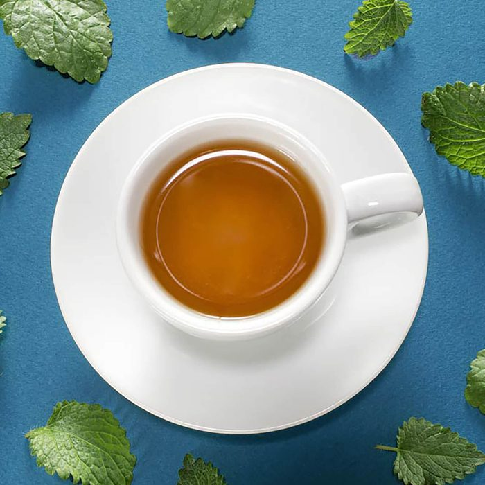 White cup of mint tea with fresh meant leaves on blue background.