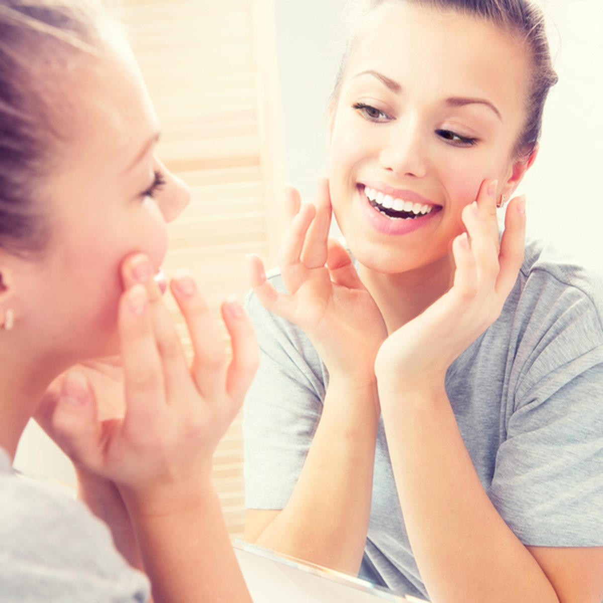 Young beautiful teenage girl touching her face before the mirror