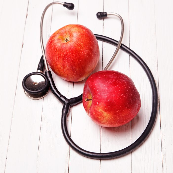 Medical stethoscope and red apple on a white table