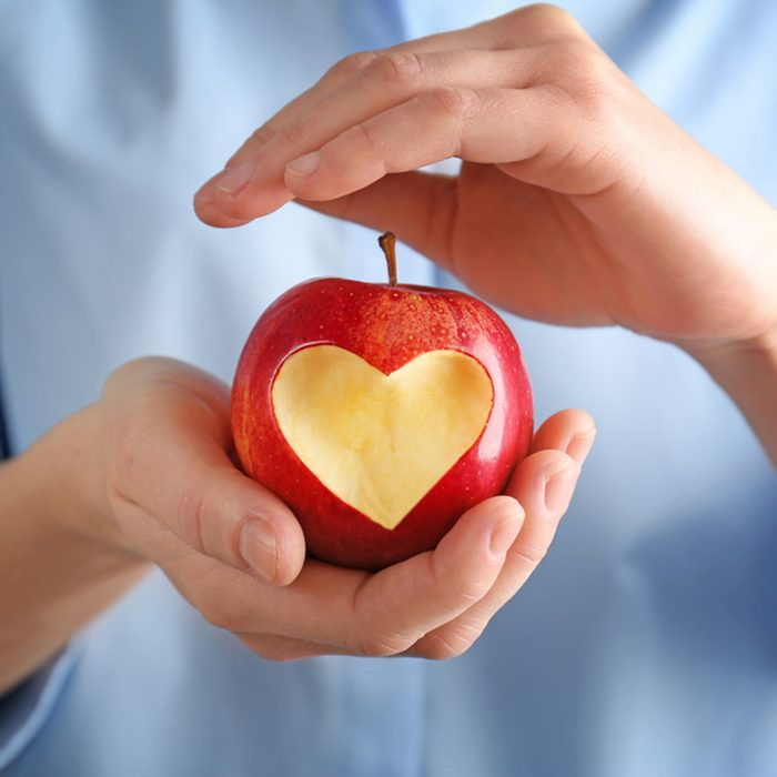 Woman hands holding fresh red apple with heart-shaped cut out